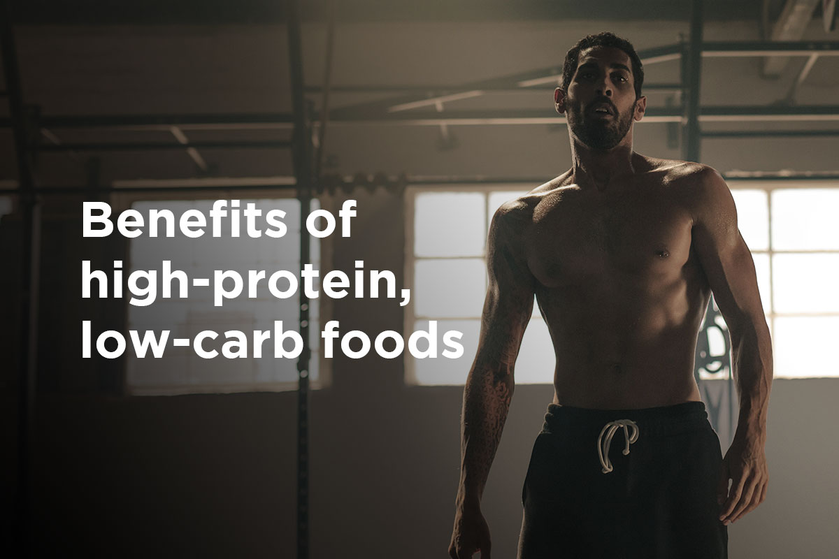 "A ripped man in training shorts standing in the gym, windows behind his back so the picture is darkened. On the left, title ""Benefits of high-protein, low-carb foods"" is written."