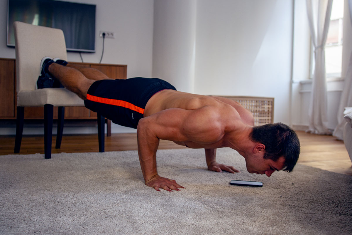 Ripped man in training shorts and sneakers, doing pushc ups in a modern apartment decoreted in beige and brown shades. His hands are placed on a beige carpet, and feet elevated on a beige chair. His elbows are bent on a 90-degrees. He is looking a the floor, and his cellphone is placed on a carpet next to him.
