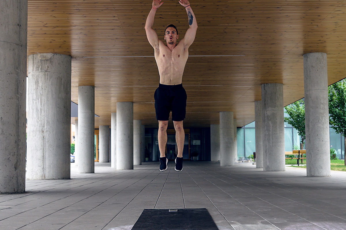 Ripped man in trainging shorts and sneakers, facing camera. He is in a yard of a big building, surrunded by a poles. The picture is taken in a mid air portion of a jump, his body fully extended, arms over head.