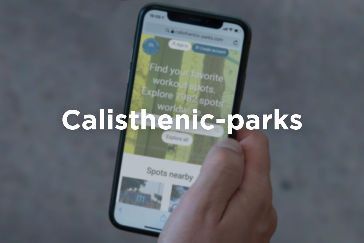 Slightly blurred picture of male hand holding a cellphone with app Calisthenics-Park opened in it. ''Calisthenic-Park'' written in a white letter over the picture.