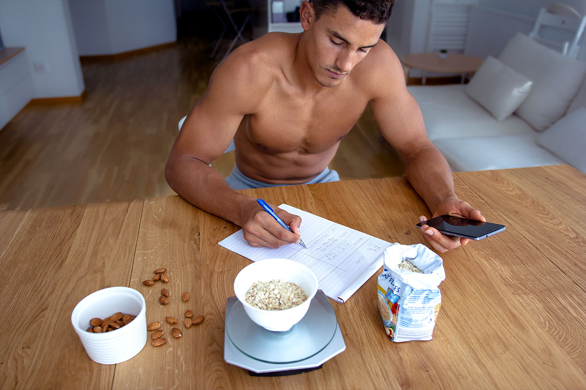 A ripped man, he is sitting in an apartment with white furniture, on a wooden table, torso naked, facing the camera. In his left hand, he is holding mobile phone. With his right hand, is is writting down something in a notebook he has on the table. In front of him, from lef to right are: a white bowl of almonds, a kitchen scale with a bowl of oats on it, and a paper bag packaging of oats.