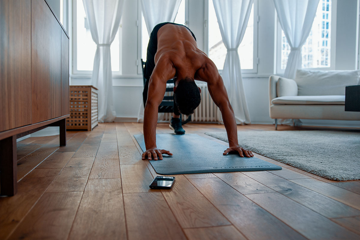 A ripped man, torso naked, facing the camera front, standin in a pike push up or downward facing dog position. His feet and palm are touching the floor, his hips are elevated from the floor so his body is formin an upside down letter V. He is in a living room of a modern apartment, no the mat, and his cellphone is lying next to him.