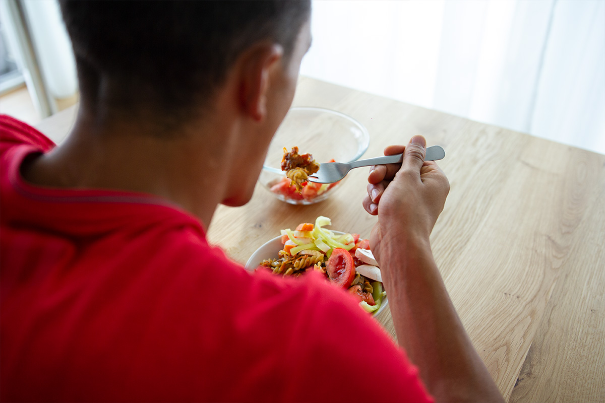 Man in red shirt, seen from behind, eating a tomato and lettuce salad.