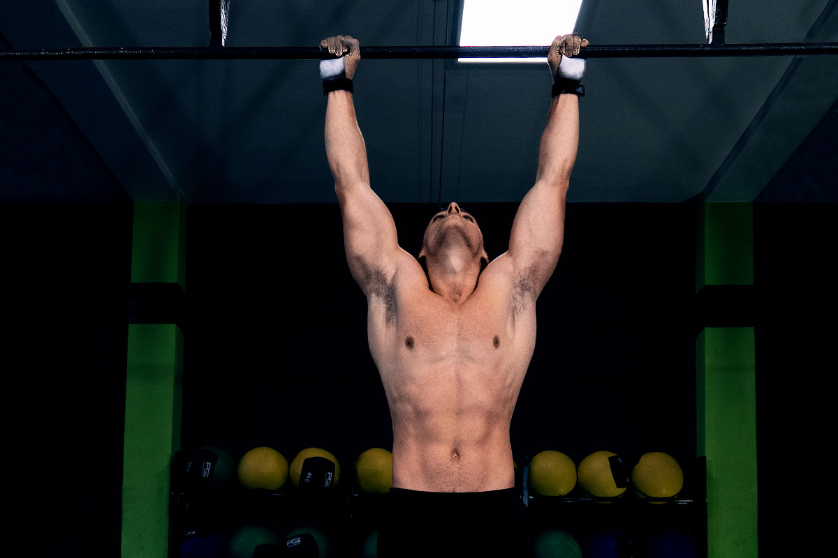 Ripped man, torzo naked, arms extender over the head, shoulder width appart, holding on to a pull-up bar, looking towards the bar.