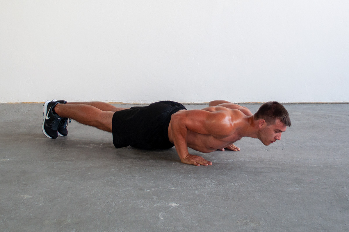 Man lowered into push up position, with hands shoulder width apart