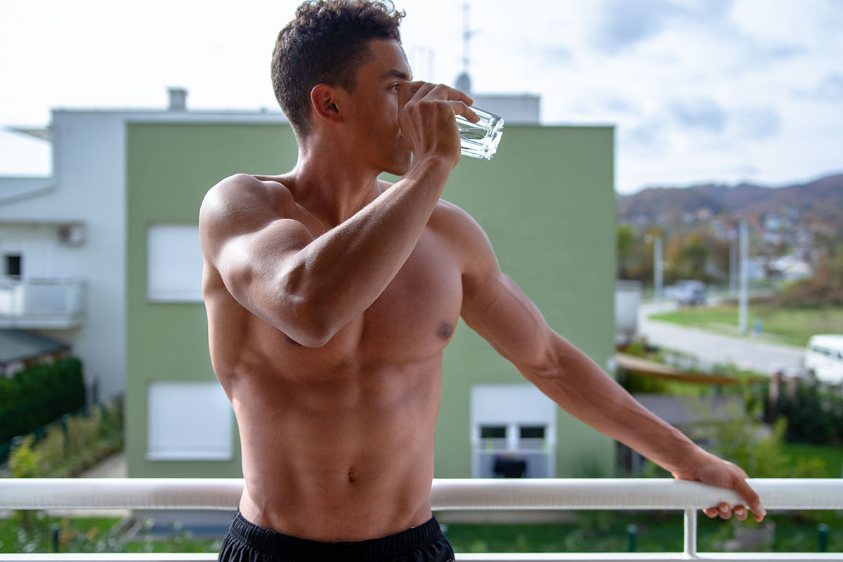Ripped man, naked torso, standing on a bacony, drinking glass of water with right hand, left hand holding on for a fence, apartment building and park in the background
