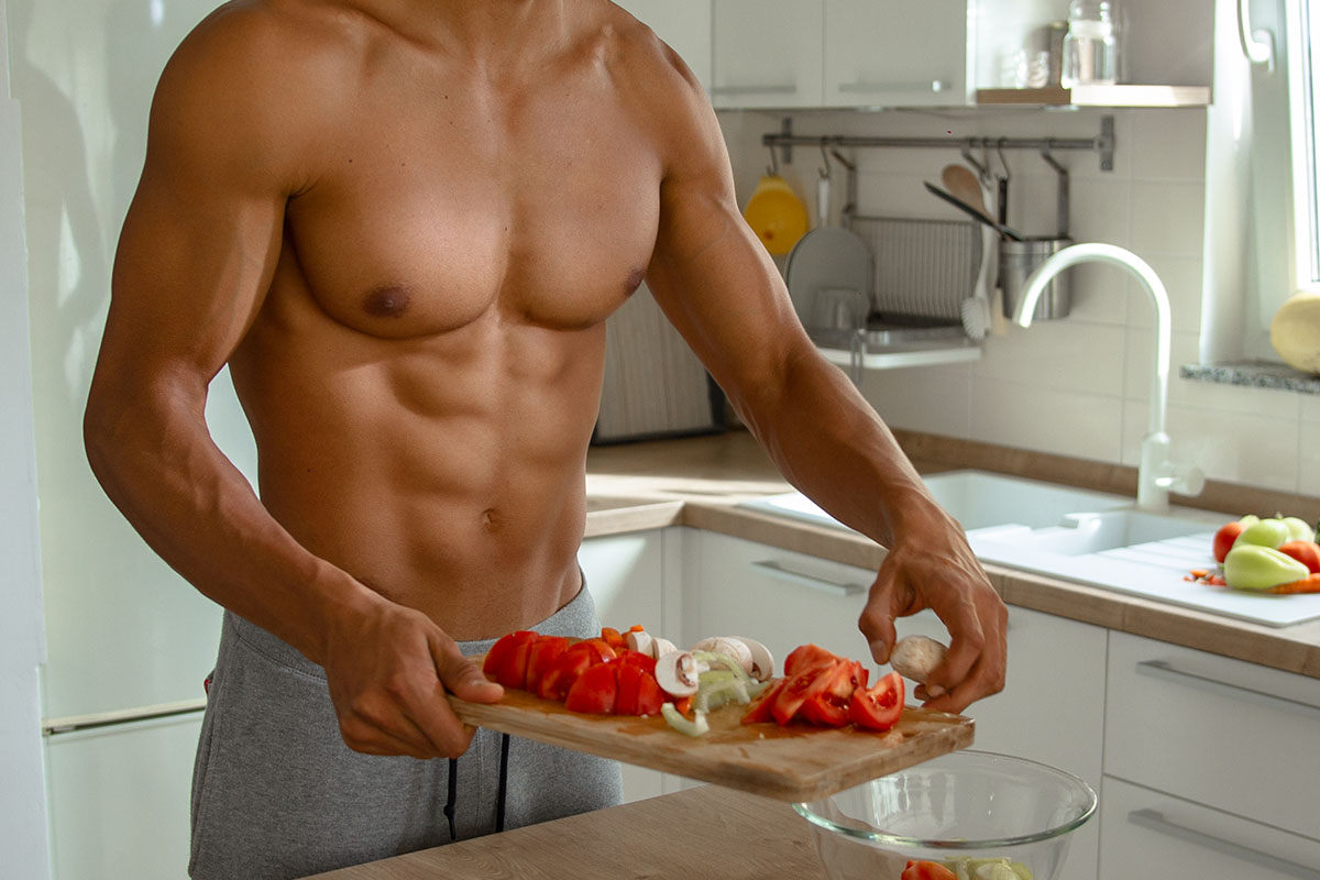 A ripped man, torso naked, in a white kitchen. He is holding a wooden chopping board, there are different vegetables sliced on it: tomatoe, paprika and mushrooms. He is putting vegetables from the boadr in the glasss bowl on the table.