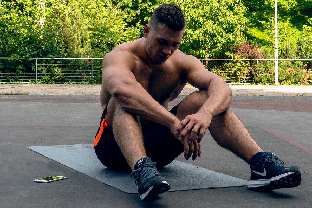 Ripped man, sitting on the mat in the playground, cellphone next to him. His elbows lying on his knees, tired from exercising.