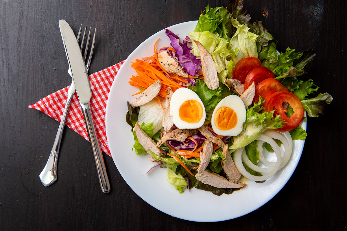 A white plate on which a salad is placed, ingredients are mixed together and one can see - lettuce, grated carrot, onions, tomatoes , and fried chicken breast pieces. On the top, two halves of hard boiled egg are placed. Next to the plate, there is a fork and a knife (on the left side). Everything is placed on a background made of dark wood.
