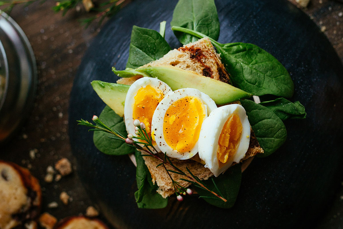A piece of toast placed on a lamb's lettuce. On that toast, there are 3 slices of avocado, and 3 slices of hard boiled egg. The toast is placed on a black plate, on a dark wooden table.