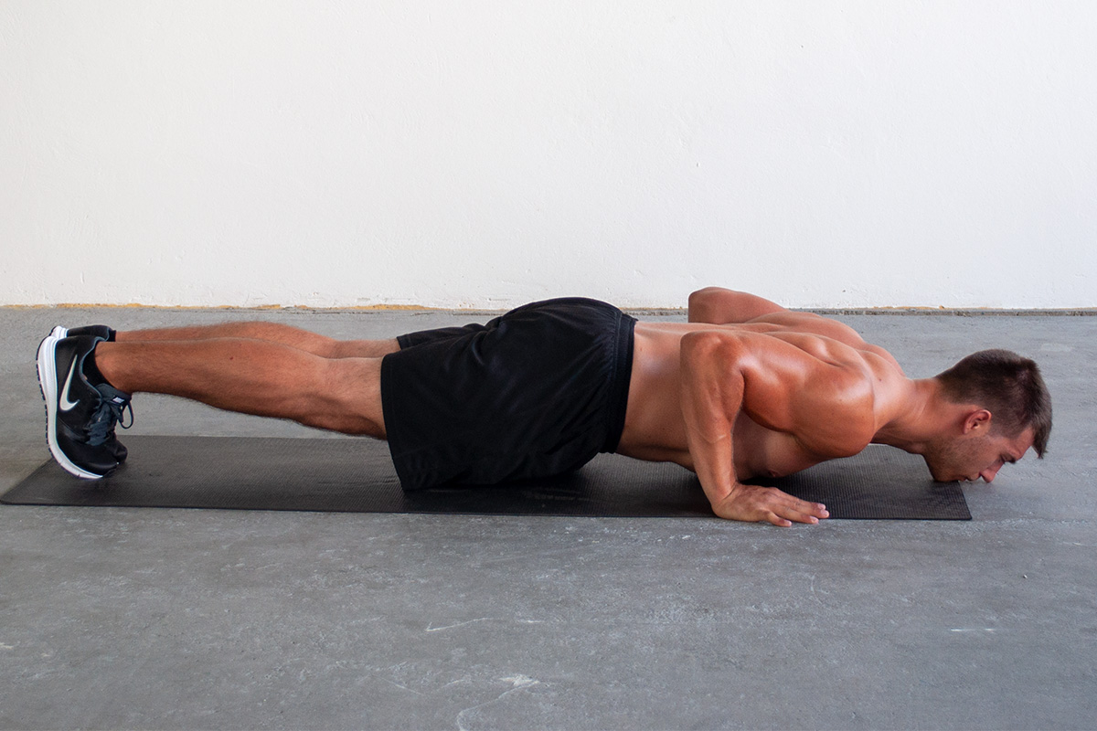 Man lowered into push up position, touching the floor with his chin