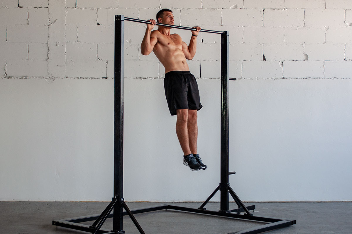 A ripped man in training shorts and sneakers, standing in a vast room, white wall visible behing him. There is a free standing pull up bar in the room, and he is holding a pull up hold position on that bar (arms holding for a bar, slighltly more than shoulder width apart, elbows bent, he is pulling his chin over the bar). He is facing the camera.