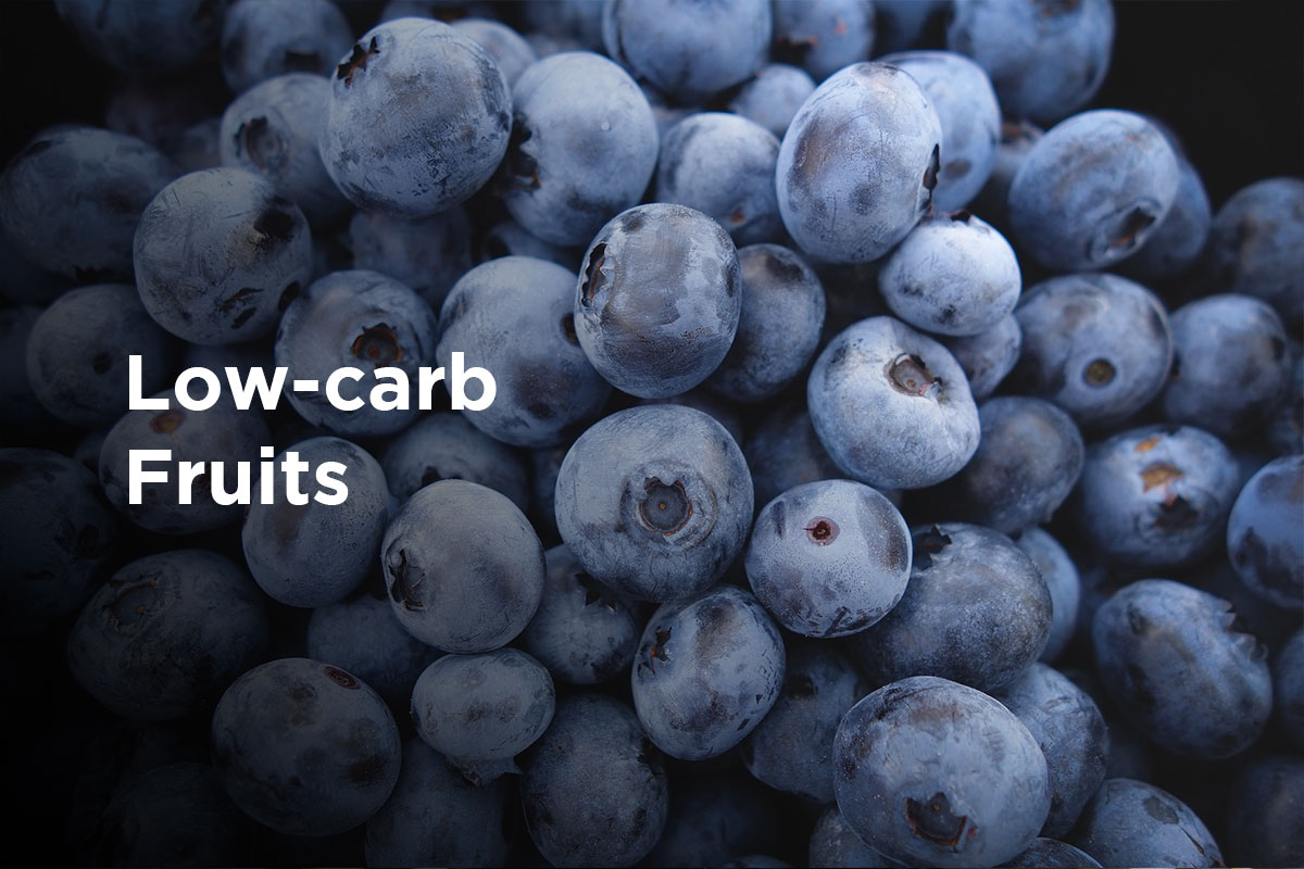 "A heap of blueberries, title ""Low-carb fruits"" written in white on the left side of the picture."