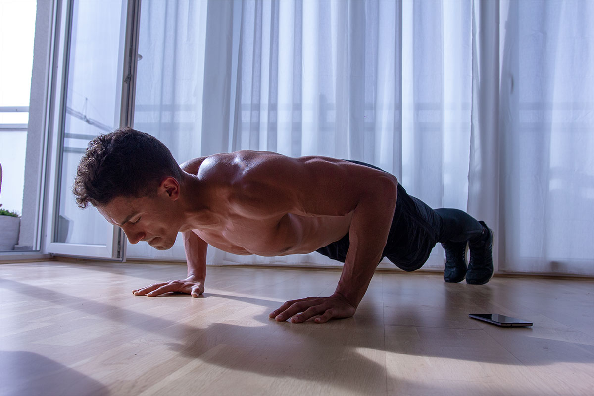 A ripped man, torso naked, facing the camera with his left side. He is standing in a push up hodl position - he is parallel to the floor, his toes and palms are on the floor, arms bent in 90-deree angle, so his body is about 20cm elevated off the floor.