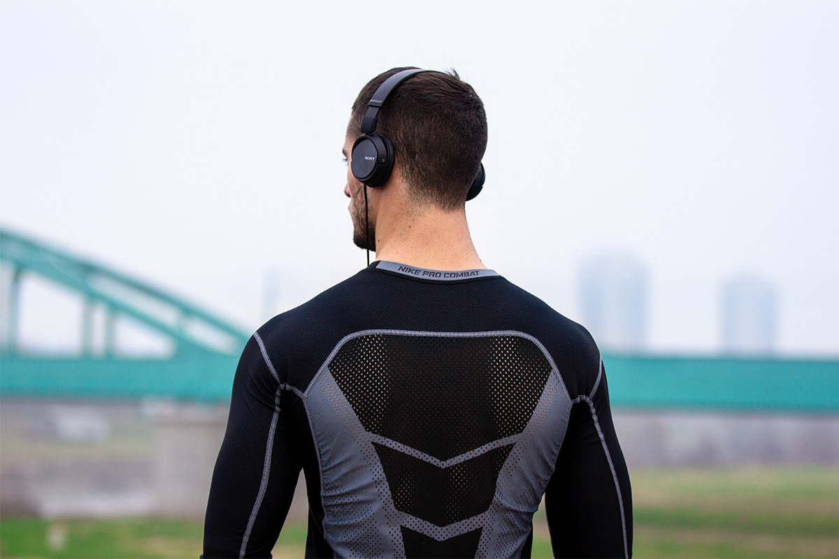 Man in the city, seen from behind. Wearing sports t-shirt and headphones.