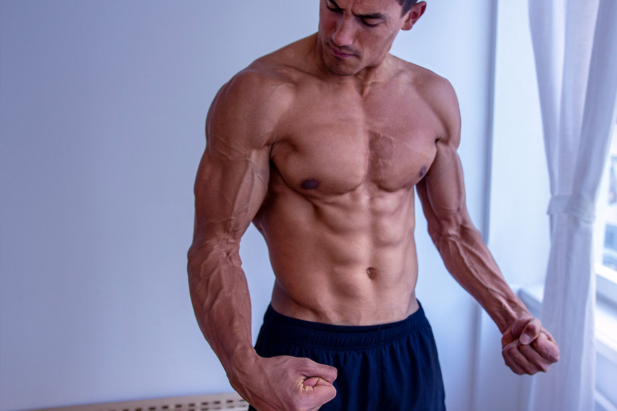 Ripped man, naked torso, fleksing his arm muscles.