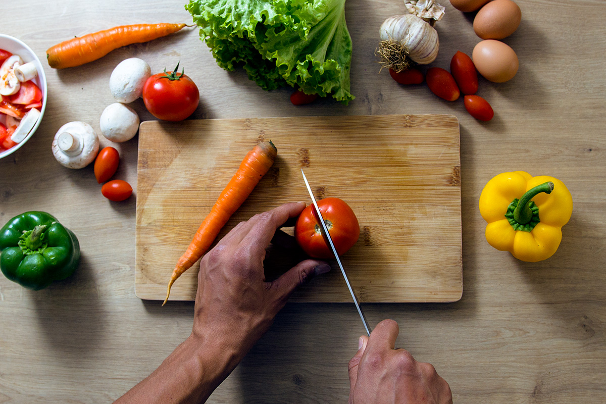 Wooden table with wooden chopping board, vegetables and eggs lying aroun it, two male hands seen holding the knife and cutting tomatoe.