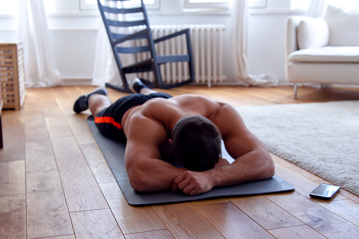 Fit man in sports equipment lying on a yoga mat on his belly, head resting on the hands, facing the mat, phone by his side