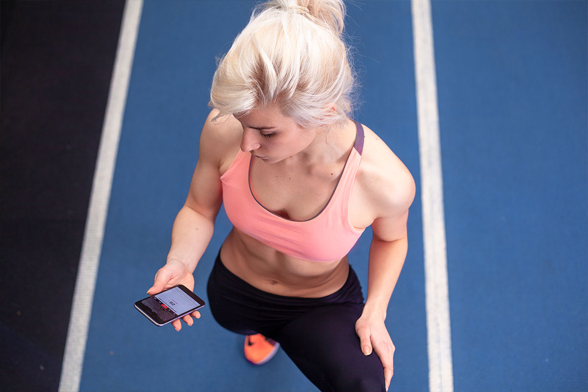 A blond fit girl, camera is looking at her from above, she is wearing pink sports bra and sneakers, as well as black joga pants. In her right hand, she is holding a cellphone. She is standing on a blue running track.