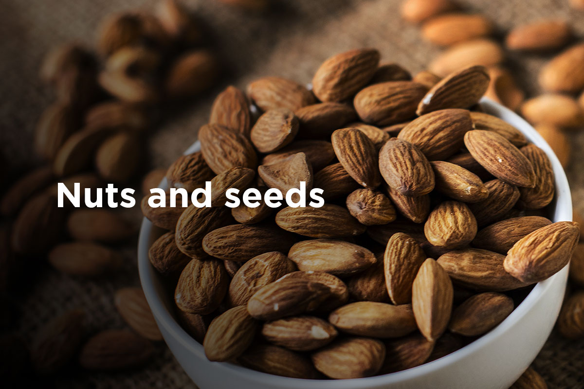 "A bowl of almonds, title ""Nuts and seeds"" written on the left side of the picture."
