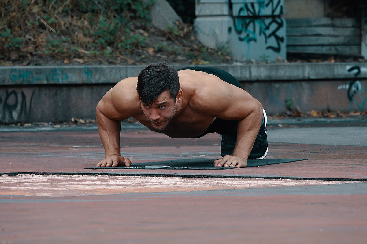 ripped man in training shorts and sneakers, facing the camera, in a push up hold position. Palms and toes toucing the floor, back straight, elbows bent in 90 degree angle and slightly away from torso.
