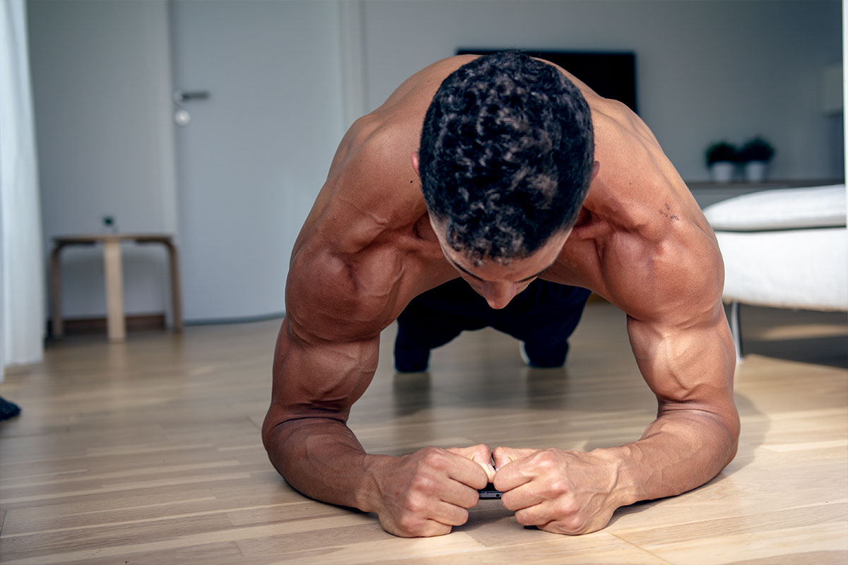 Ripped man i a training shorts in a livingroom of the apartment decorated in white and grey. He is facing camera in a plank position - hiy body straight and parallel to the flor, his toes and forearms are touching the floor. Shoulder and arm muscles flexed.