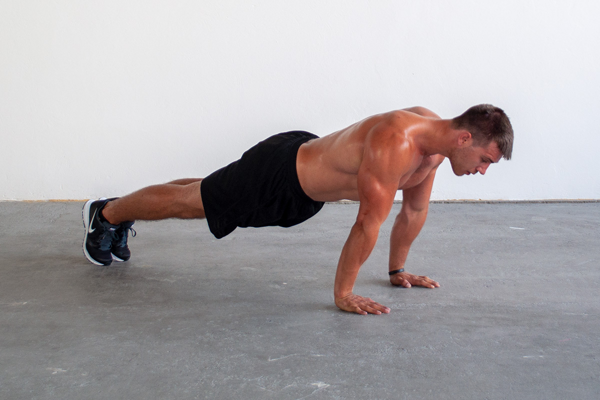 Man in fully extended push up position with hands shoulder width apart