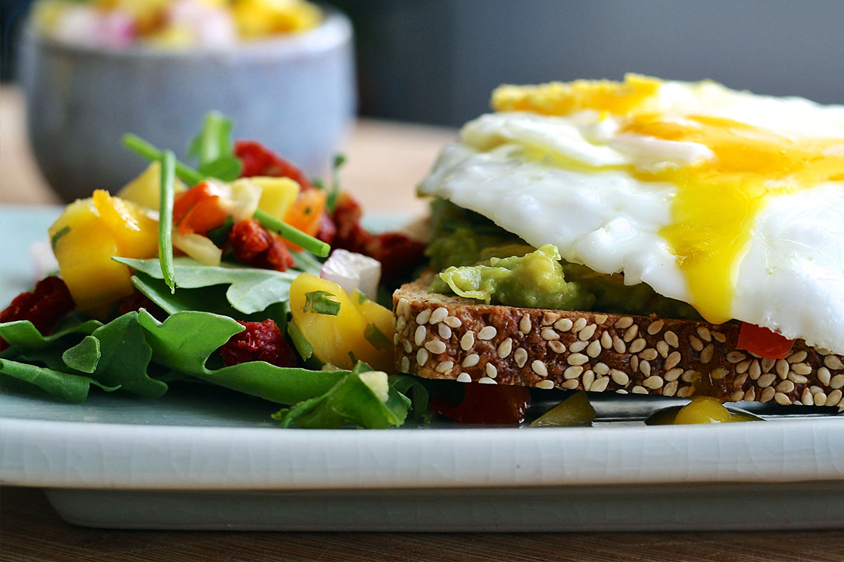 A plate with food on it. On the left, there is a mango and lettuce salat, on the right a slice of brown bread  with mashed avocado and fried egg on the top.