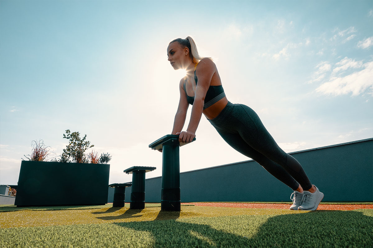 A blong girl, wearing grey yoga pants, sports bra and snekares, She is in an outdoor space, what seems to be like a rooftop with a grass surface and atheltic trail on the edge, near the fence. There are three small benches, and she is leaning with her hands on one of those benches, standing in an incline push up position (hand straight and inclined on the bench, body staight).