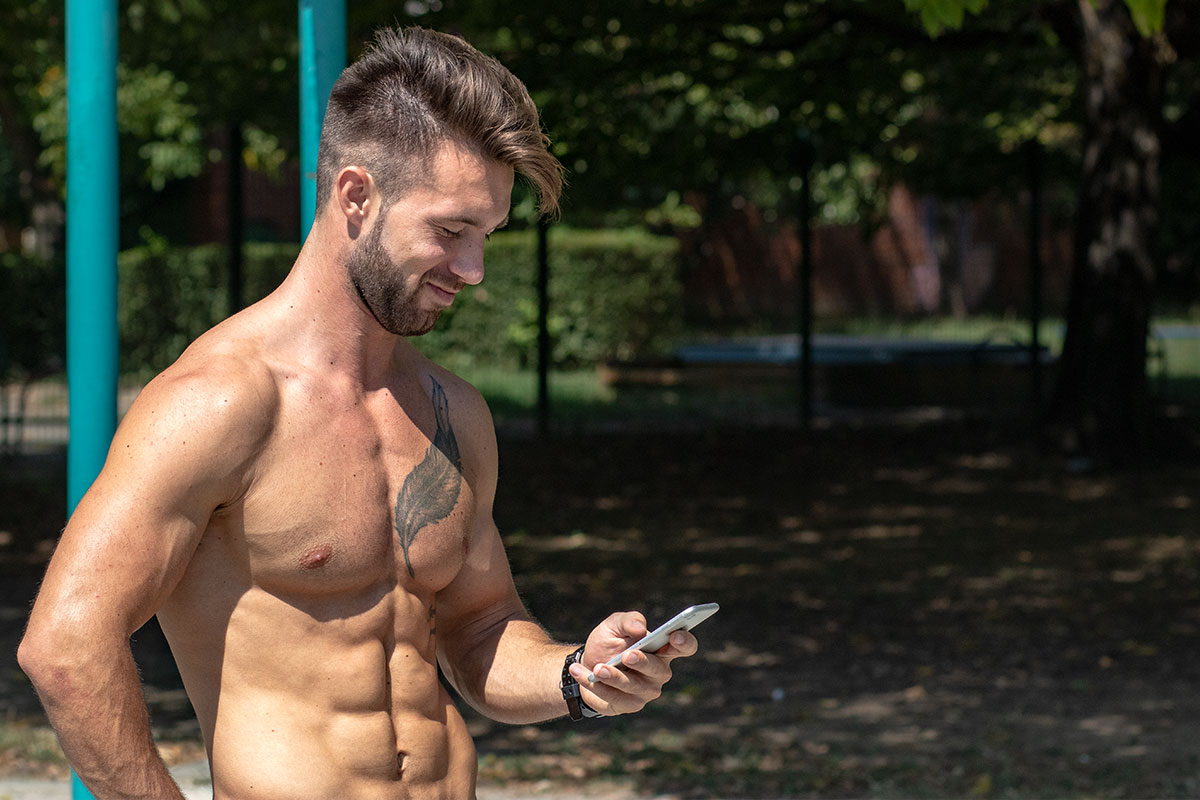 A ripped man, only upper body shown on the picture, standin in a workout park in the nature, holding and looking at the mobile phone in his right hand.