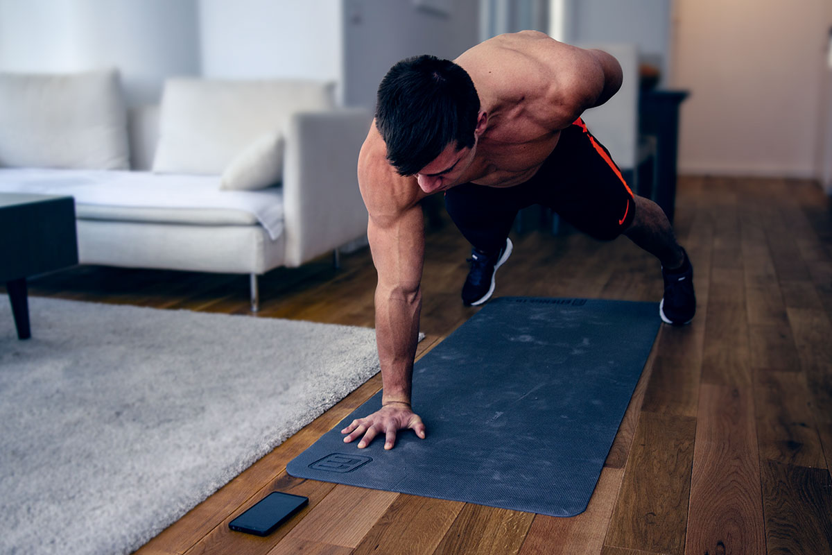 A ripped man in training shorts and sneakers, faing the camera forwards, standing in a one-arm-push-up position. Left arm bent behind his back, palm of the straightened right arm and toes touching the floor, back straight.