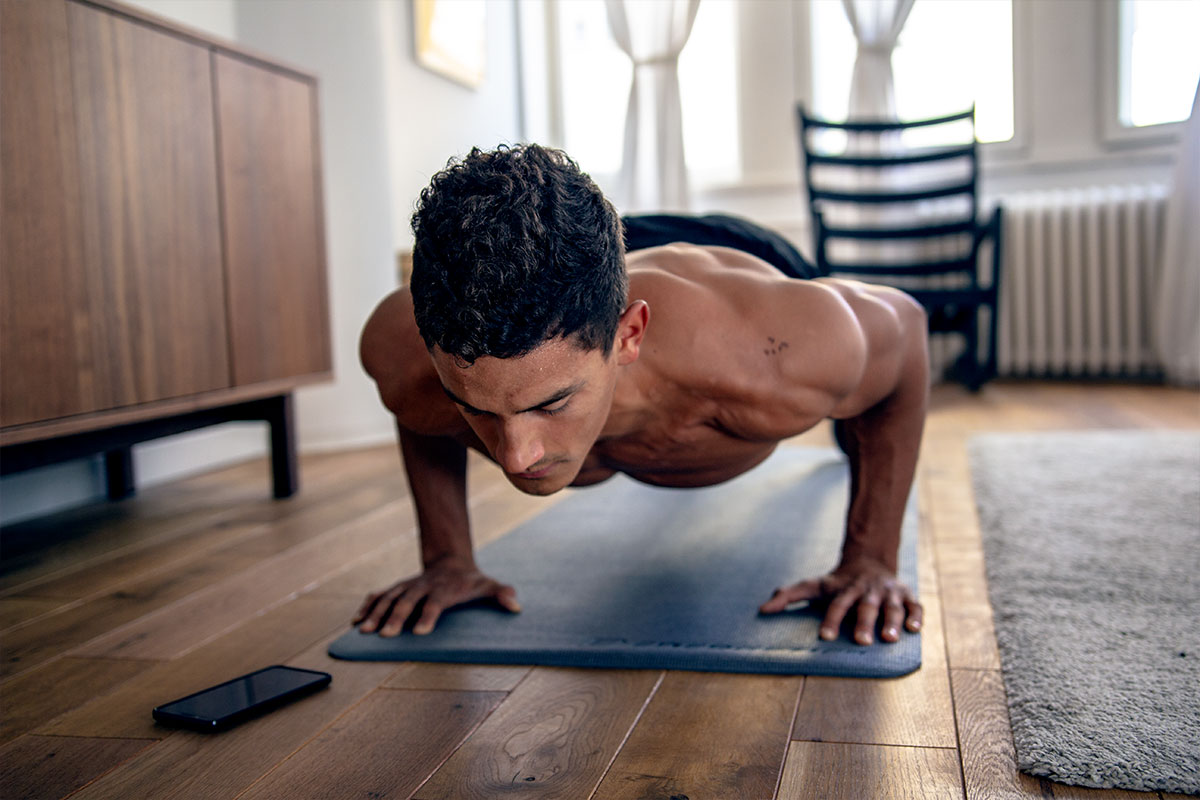 Ripped man in an apartment livingroom, wearing trainging shorts. He is facing the floor, his palms and toes are on the floor, his body straight and parallel to the floor, his elbows bent. The exercise he is doing is called push up hold.