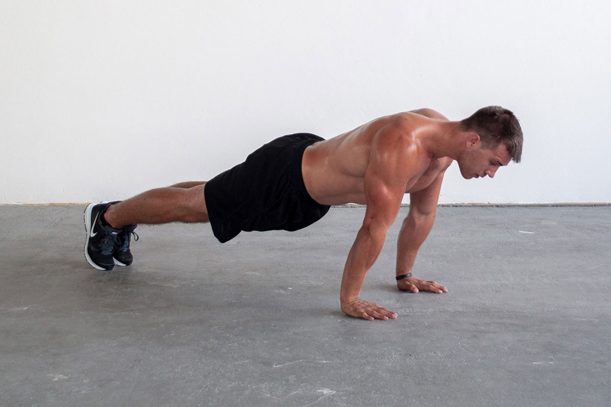 Ripped man in trainging shorts and sneakers, standing in a plank position (toes and palms touching the floor, body and arms straight, face facing the floor. He is facing the camera with his right side.
