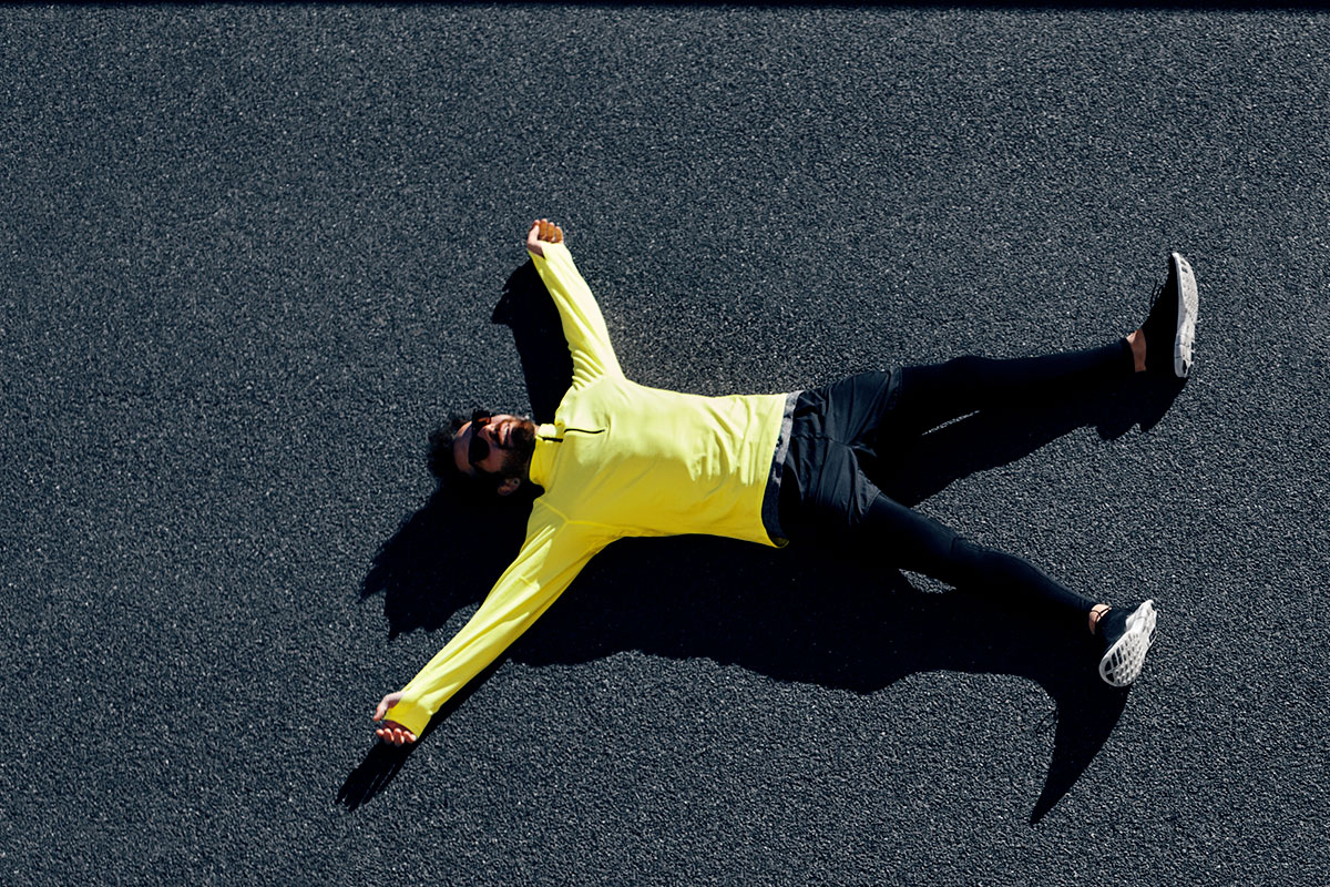 A man in a yellow long-sleeved sports shirt, black long sports tights, and black sneakers, lying on a playground floor, arms and legs extended in a starfish position.