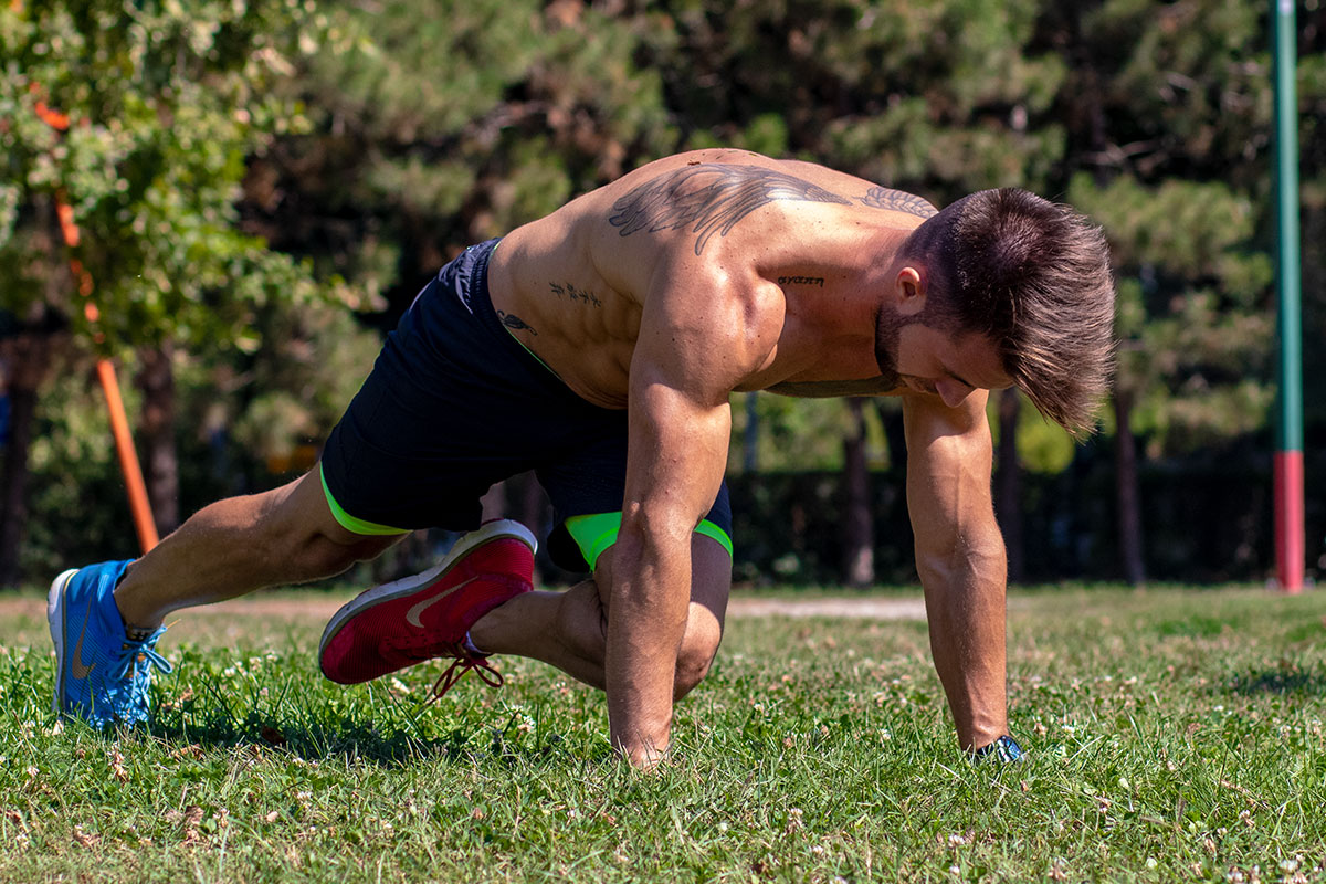 Man in fully extended push up position, left leg raised, left knee reaching for rigth elbow
