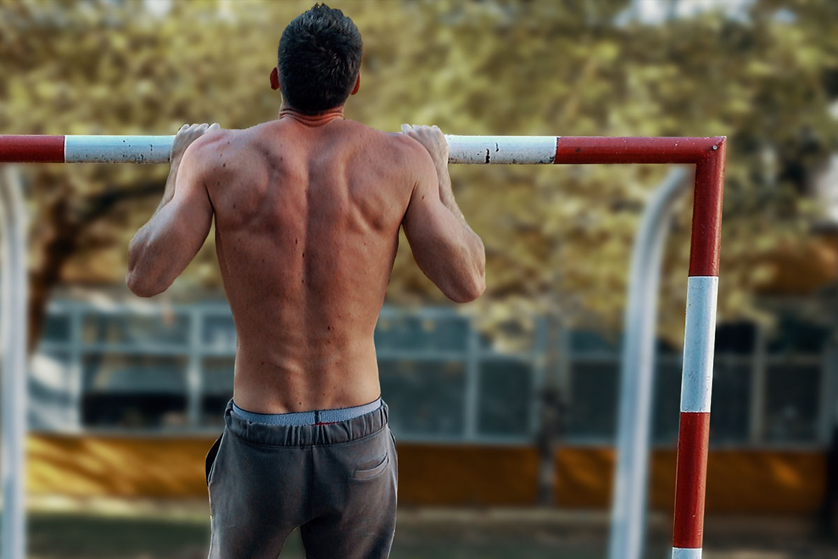 a ripped man in training shorts, ouside in a park. He is stading in a pull up hold position using an empy frame of soccer goal as a pull up bar. Pull up hold position: (arms holding for a bar, slighltly more than shoulder width apart, elbows bent, he is pulling his chin over the bar).