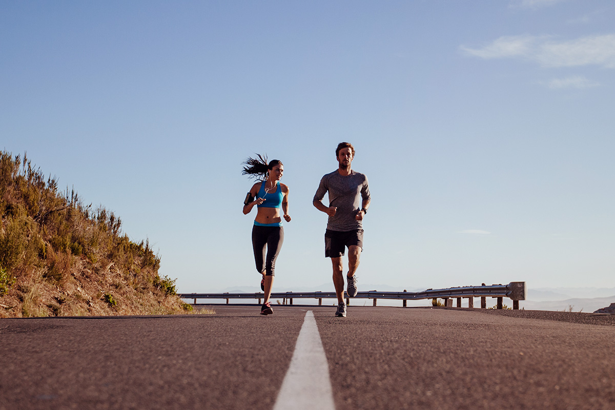 man and woman in sports equipement running on empy highway