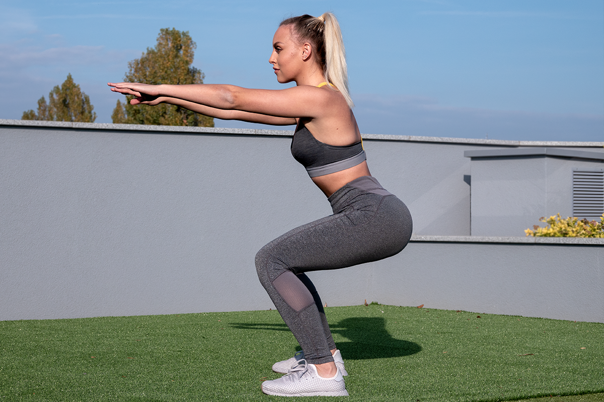 A blonde girl in a grey yoga pants, sports bra and sneakers. She is standing in a squat position - knees 90 degrees bent, back straight, arms extened forward. She is facin the camera with a left side of her body. She is standing on a building rooftop, on a grass sufrace, behind her, a concrete fenc of the buidling is visible, along with some tree tops behind it.
