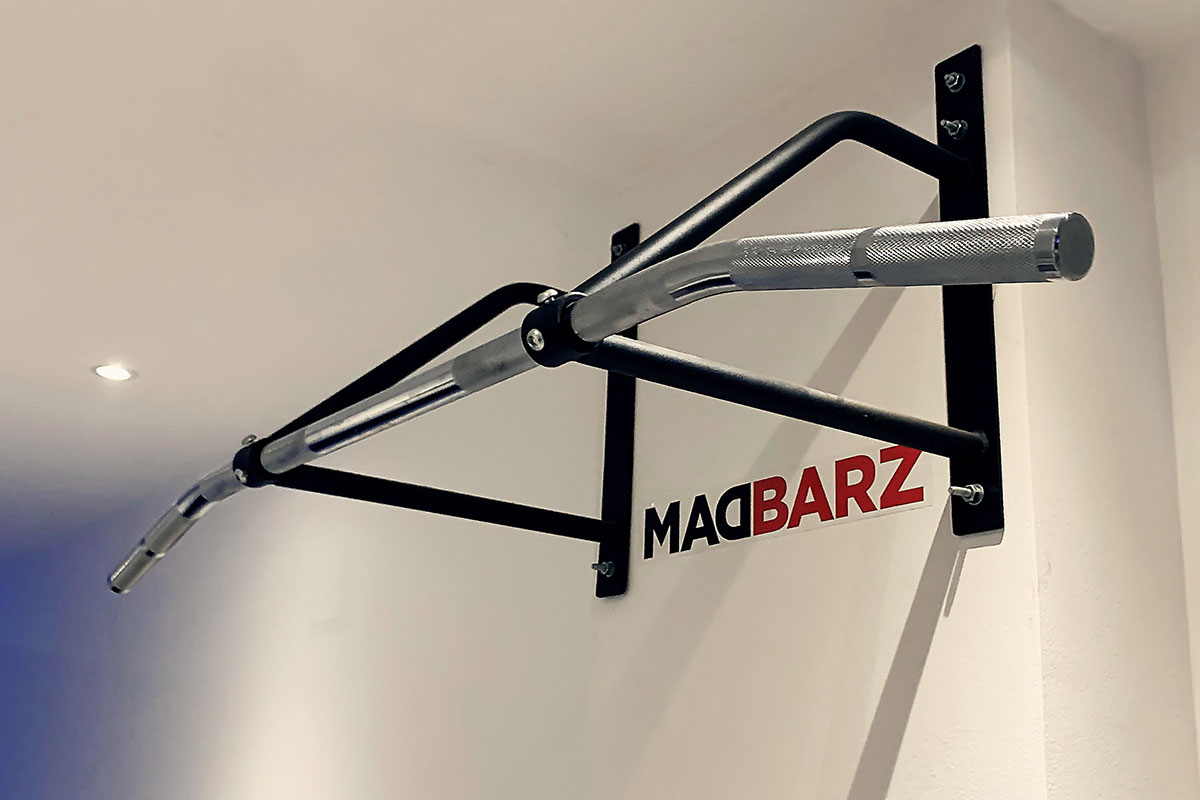 A wawll mounted pull up bar set on a white wall, with Madbarz sticker underneath it.
