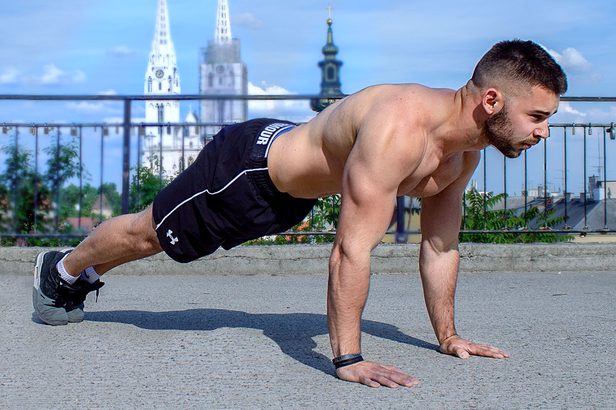 Ripped man in shorts and sneakers, facing camera with his right side, in a plank position. Toes and palms touching the floor, back and arms straight.