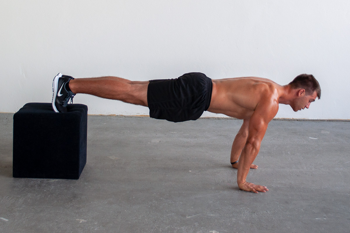 Man in fully extended decline push up position, with legs elevated on a box