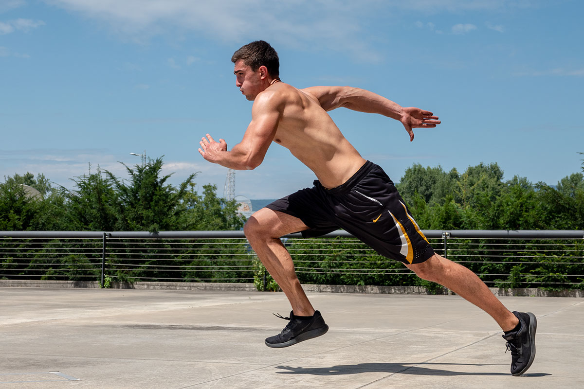 A ripped man, wearing training shorts and sneakers, torsko naked, sprinting on the concrete floor. Behind him, ther is a  fence visible, as if he is on an elevated surface. Behind the fence, one can see tops of the trees and some parts of urban landsacape visible throught the trees.