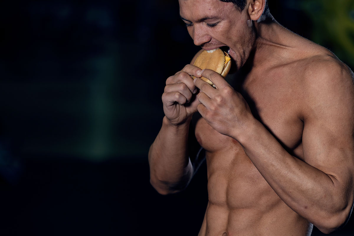 Ripped man without a shirt, taking  a first bite of the cheeseburger, holding it with both hands, eyes closed.