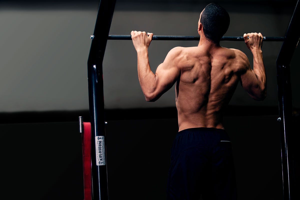 Ripped man, torso naked, he is standing in a darkened room, only him and pull up bar visible. He is standing in a puill up hold position, facint ht ecamera with his back (arms holding for a bar, slighltly more than shoulder width apart, elbows bent, he is pulling his chin over the bar).