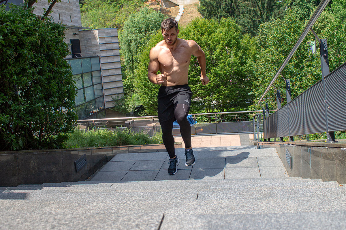 A ripped man, wearing training shorts and sneakers, torso naked. He is running up the stairs outside, in the distance behind him there are trees, as if in urban park, and on the left side of the picture urban villa is visible.