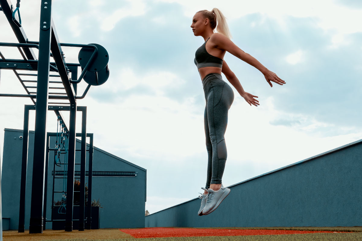 A fit blonde girl, posing the camera with her left side, in a grey yoga pants, sports bra and sneakers, jumping verticaly, her arms are slightly behind her bodys, he is elevated from the floor for about 20 centimeters. She is in the outside gym, bar station is visible on from her right. a concrete fence on her left and bloe sky with couple of clouds is visible behind her.