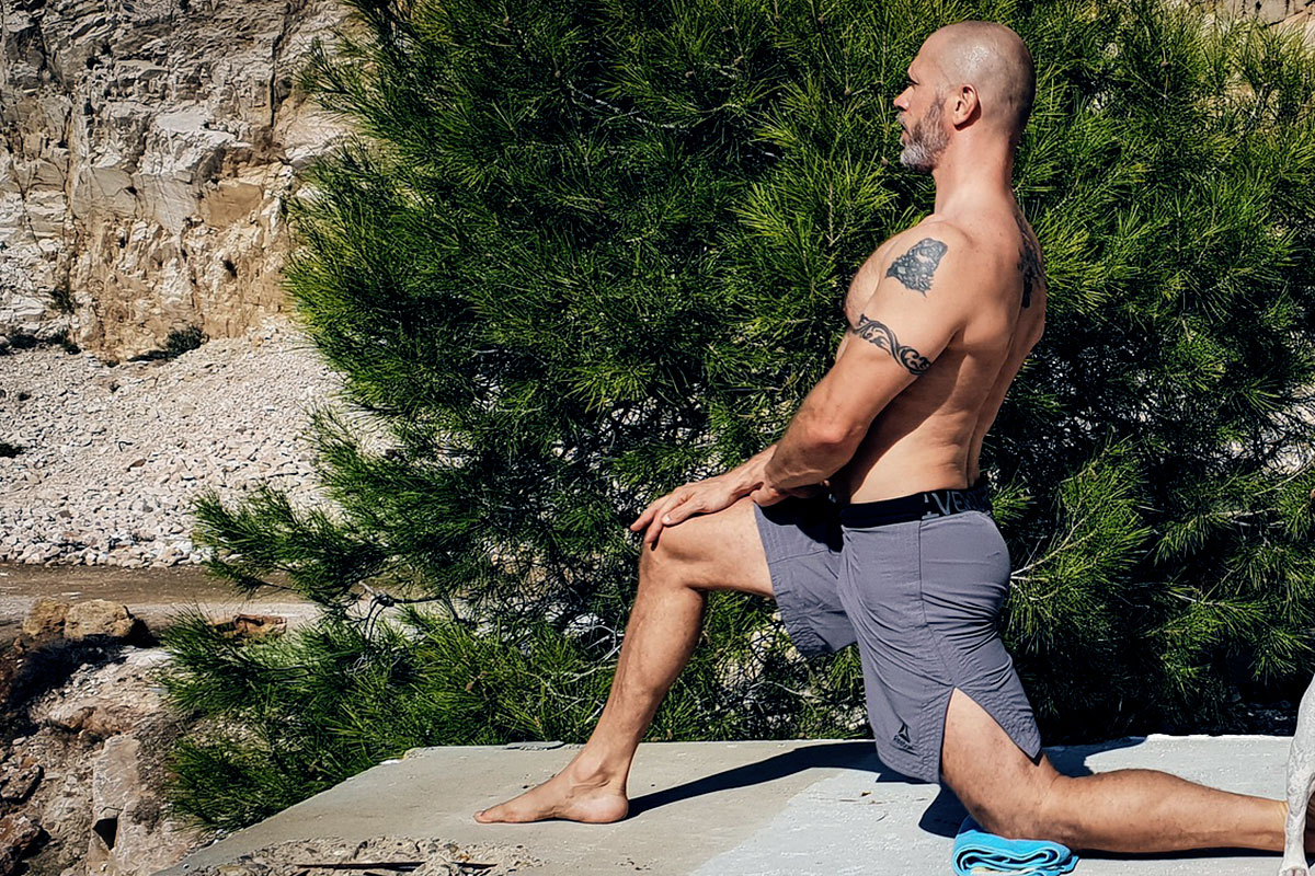 A muscular man, in grey shorts, shirtless, kneeling on the left knee, right leg in front of him, knee in slightly more than a 90-degree angle. Palms of hands placed on his right knee, looking forward (yoga - low lunge pose). In the background, pine trees and rocky landscape can be seen